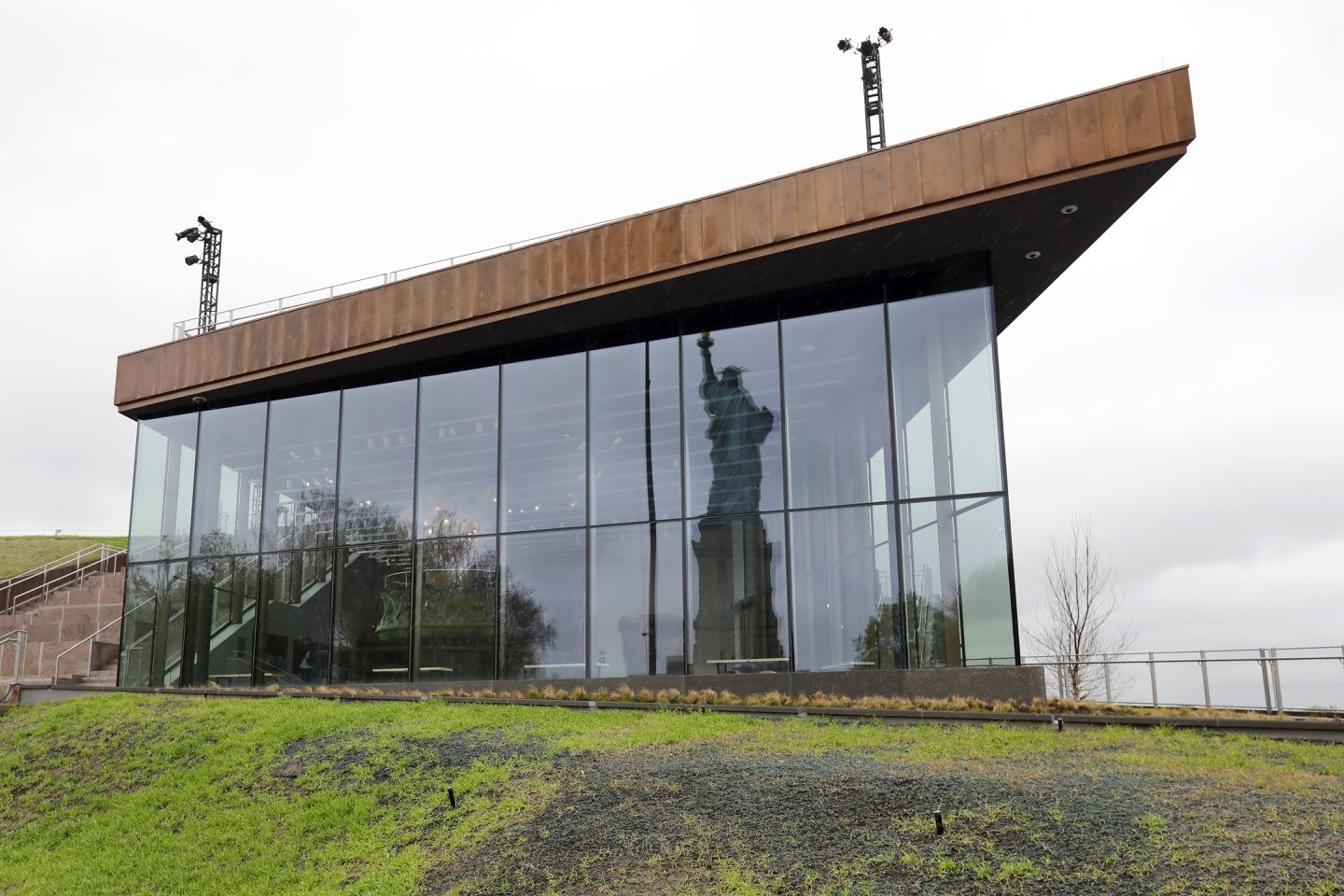 The Statue of Liberty is reflected in the windows of the new Statue of Liberty Museum.