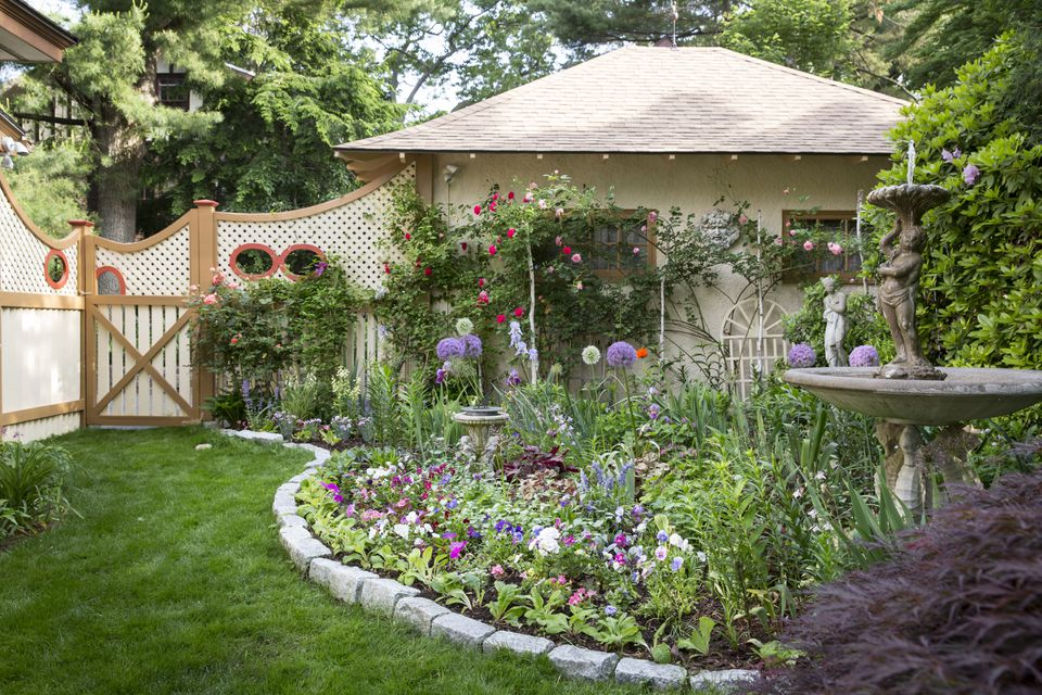 The Cupid Fountain Garden spruces up a garage with June roses and alliums.