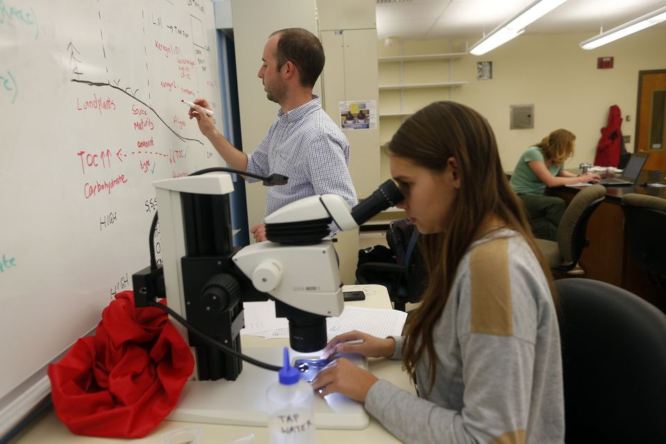 Tufts University assistant professor Andrew Kemp jotted notes on the board as Tufts junior Taylor McGinnis, 20, looked for microorganisms called foraminifera.