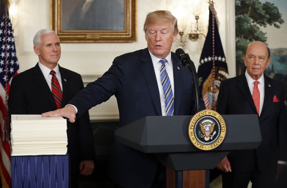 President Trump reached to touch a copy of the $1.3 trillion spending bill.