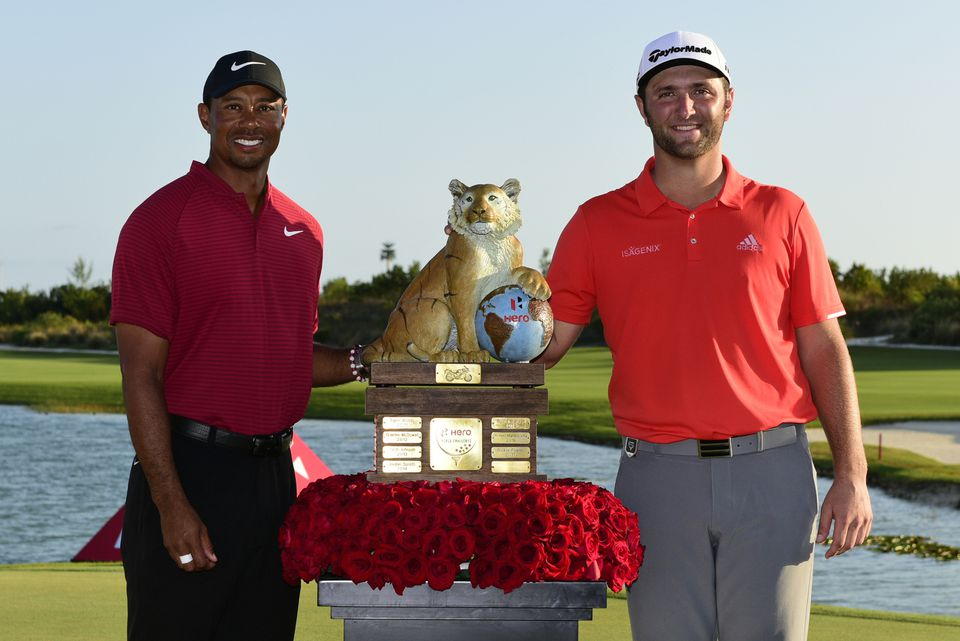 Tourney host Tiger Woods (left) poses with winner Jon Rahm and his trophy at the Hero World Challenge in Nassau, Bahamas.