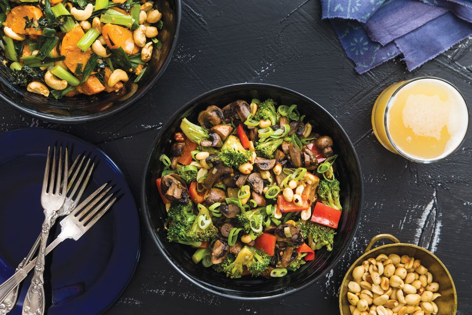 Spicy stir-fried broccoli, mushrooms, and peanuts (center); Thai-inspired red curry sweet potatoes and kale with cashews (top left).