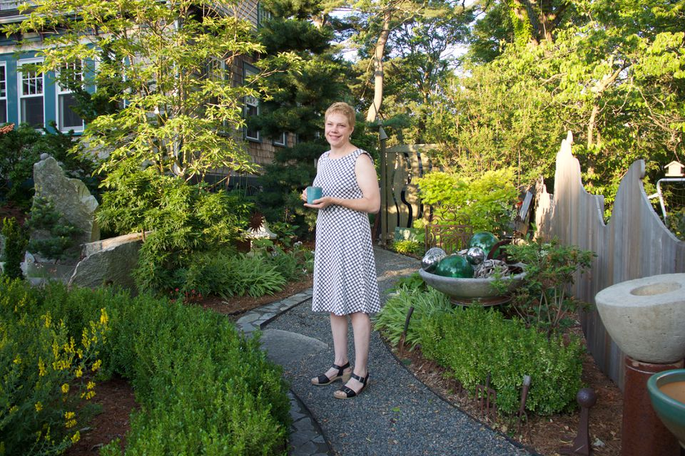 Garden designer Christie Dustman in her front yard in West Roxbury,  next to an unusual Japanese Clethra barbinervis; a concrete bowl of glass buoys and metal balls sits on an old tire rim.