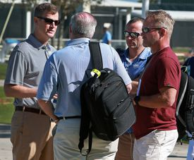 Kirk Minihane (second from right) spoke with Red Sox CEO Sam Kennedy (left) during spring training.
