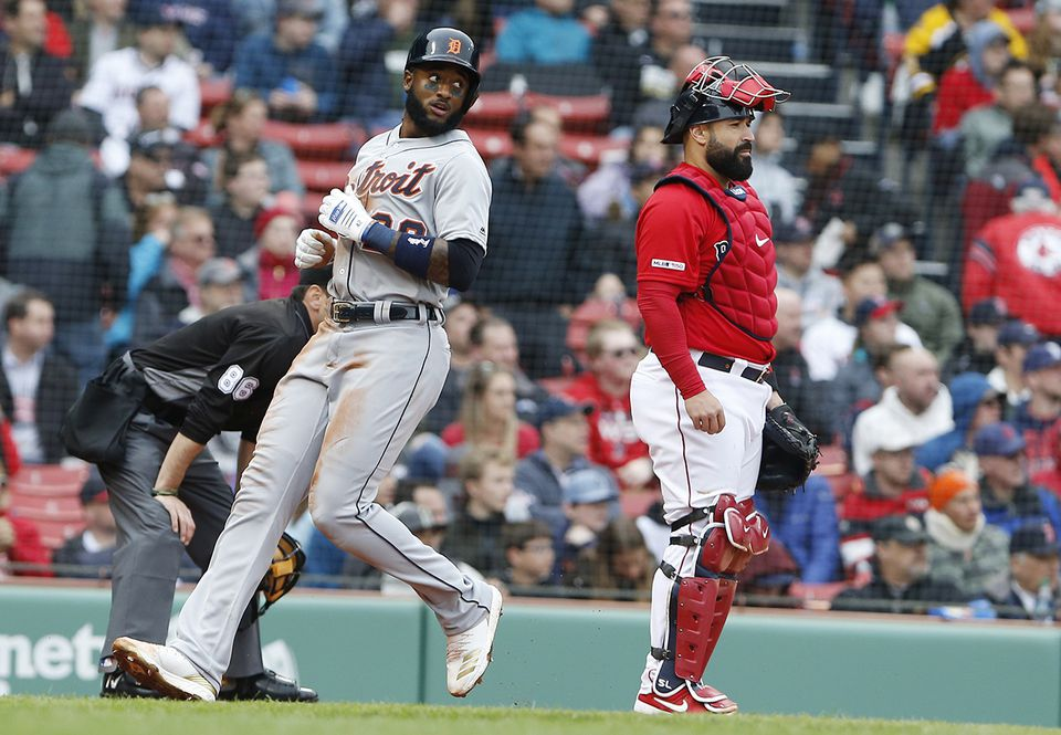 Detroit's Niko Goodrum (left) scores a fourth-inning run as Red Sox catcher Sandy Leon looks on.