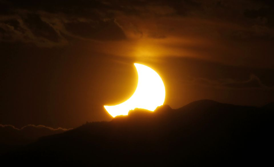 The sun set behind the Rocky Mountains, as seen from downtown Denver, during a May 2012 eclipse.