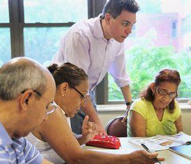 English instructor Helio Regis helps Ibere Menezes, Maria Medeiros, and Maria Isabel at Marlborough's senior center.