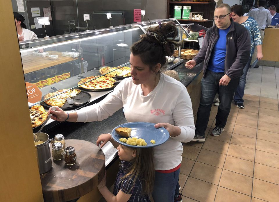 Coast Guard spouse Rachel Malcom (left) gathered for herself and her daughter at Roger Williams University this week. The college offered a free dinner for active-duty Coast Guard members and their families who are working without pay during the federal shutdown.