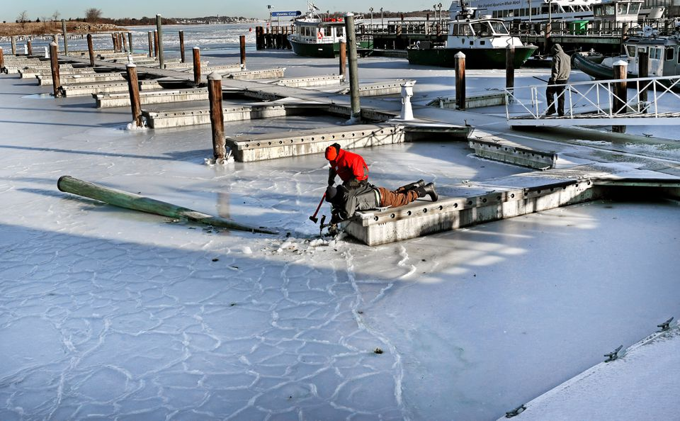 Tyler Borris and Willie Fessenden, both with Hingham Shipyard Marinas, worked to free a finger dock and a piling that snapped off in the ice.