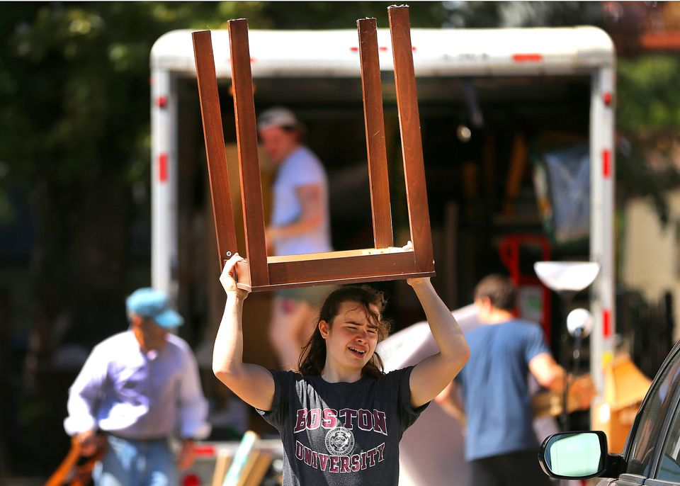 Meredith Santaus from Brighton walked to an apartment on Linden Street with a table above her head.