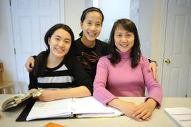 Carolyn Zhou (left, 15) sits with her sister Megan (middle, 14) and their mom Jianlin Li with homework at the kitchen table.
