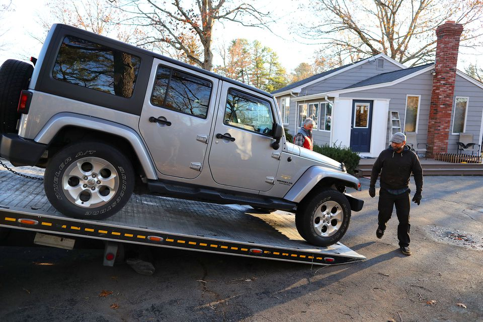 A flatbed tow truck removed the Jeep from the driveway of the home belonging to the Principal of Bellingham High School, Lucas Giguere.