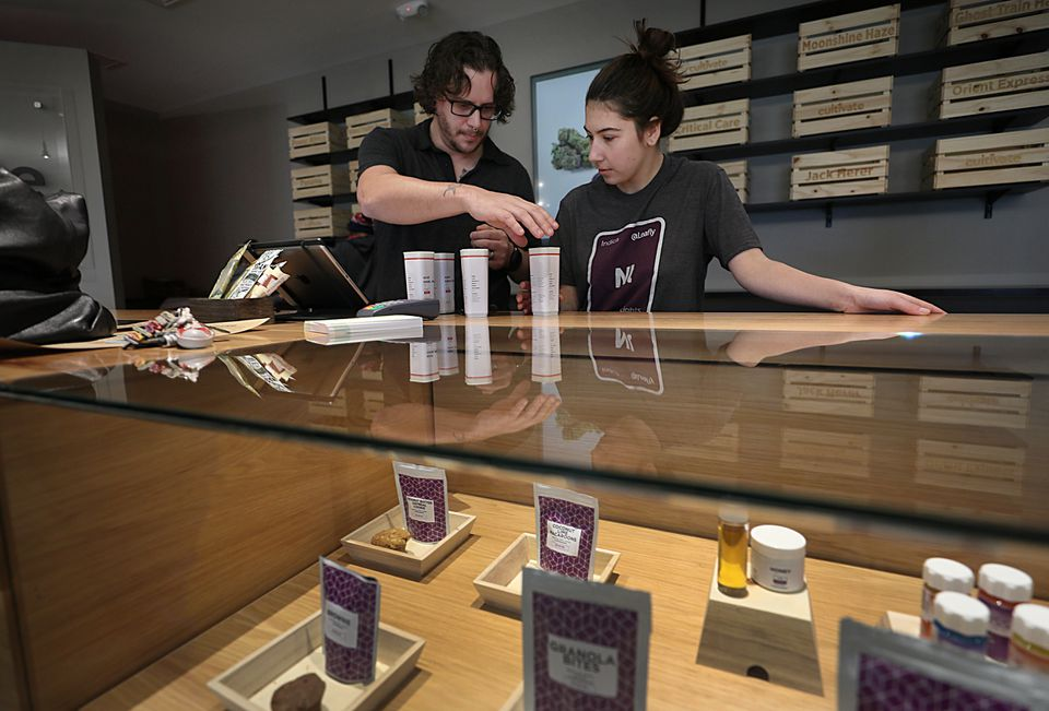 Employees, Nick Jarrin, left, and Kaylee Castell check out a customer buying medical marijuana at Cultivate.