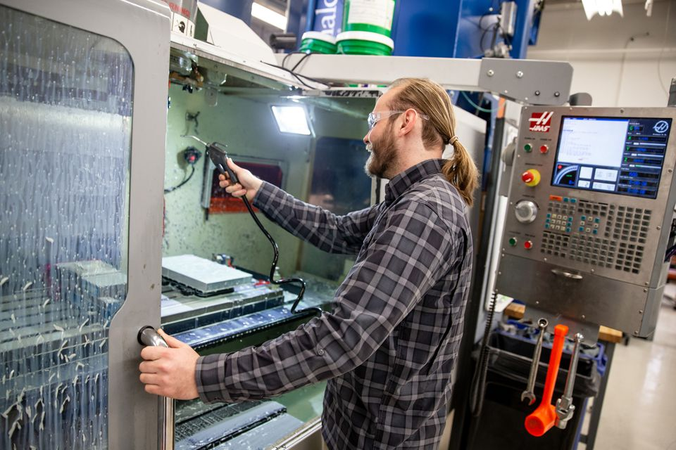 Engineer Nicholas Holmes used compressed air to clean a milling center at Voxel8 in Somerville.