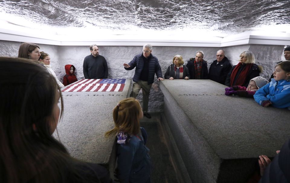 John Carroll (center) spoke to visitors of the Adams crypt in the United First Parish Church, where John Adams and John Quincy Adams, as well as their spouses, are buried.