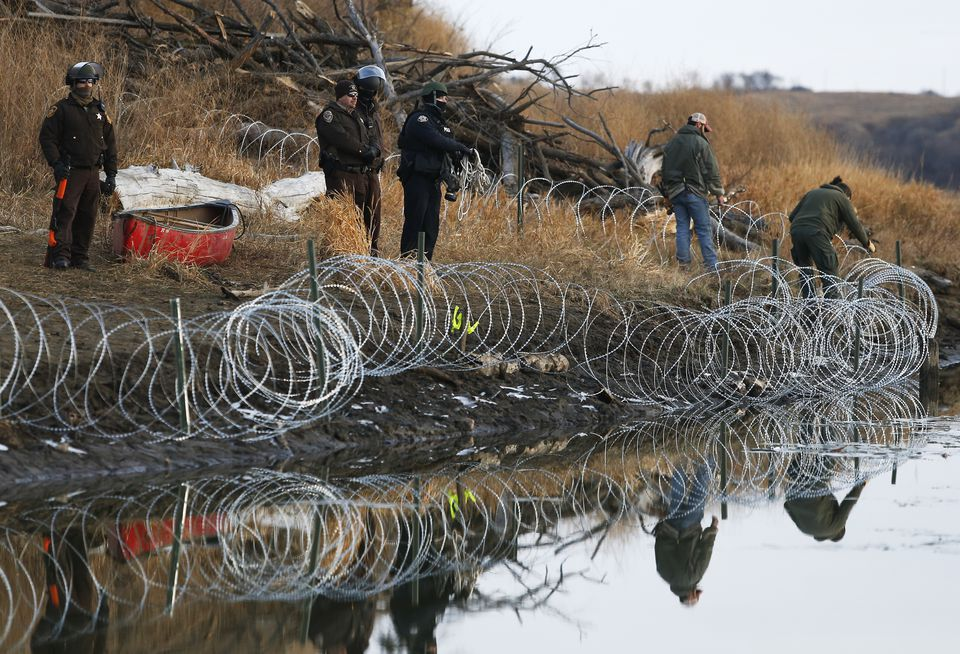 Police adjusted barbed wire that they set up on Turtle Island a day after protesters built a bridge to access it in Cannon Ball, N.D.