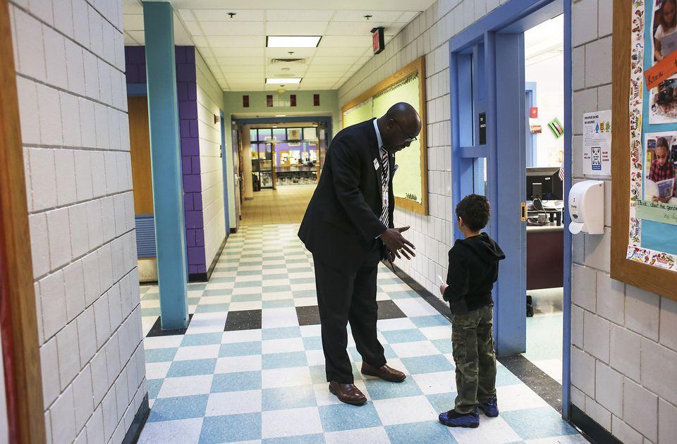 Haverhill schools administrator Rashaun J. Martin, a Boston Latin alumnus, talked to a young boy in the hallway of the district's Pentucket Lake Elementary School.
