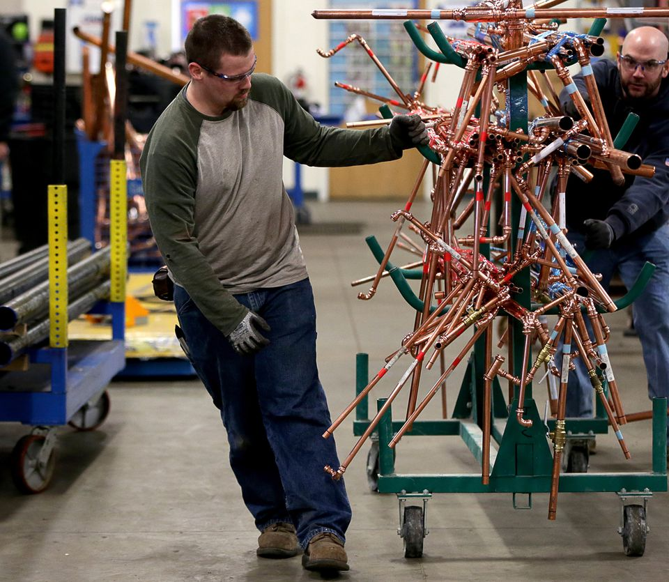 In Wilmington, plumber Brian Janiac transfers copper piping from the assembly line to a truck for delivery.