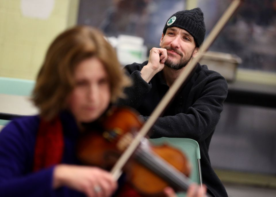 """CASPAR homeless shelter guest Kevin J. Merrill II enjoys music by Shelter Music Boston during a holiday concert. """"I love it when these guys come in. They brighten up the place, they give us hope,"""" he said."""