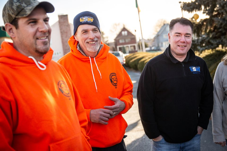 Union members David Monahan (left), Barry Johns (center) and John Buonopane talked with fellow National Grid workers as they reacted to a vote on new contract.