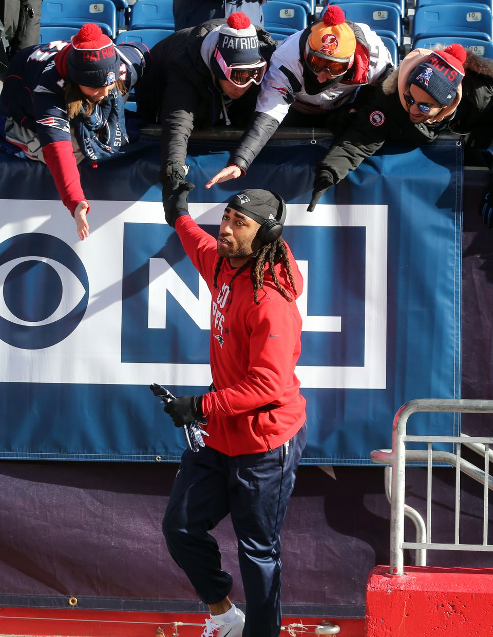 Patriots cornerback Stephon Gilmore high fives fans before the game.