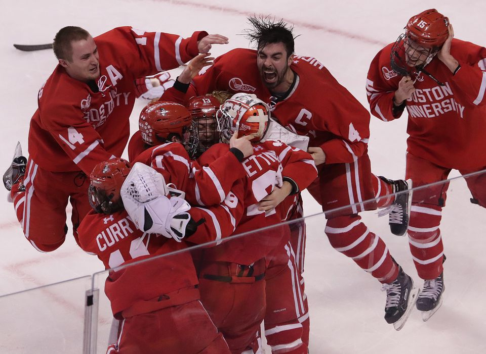 BU goaltender Jake Oettinger (29) is at the center of the celebration as captain Brandon Hickey (4) and Bobo Carpenter (14) come flying in after the Terriers beat Providence, 2-0, to win the Hockey East championship.