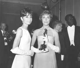 Julie Andrews, holding her Oscar statuette, posed with Audrey Hepburn backstage at the 37th annual Academy Awards ceremony, 1965.
