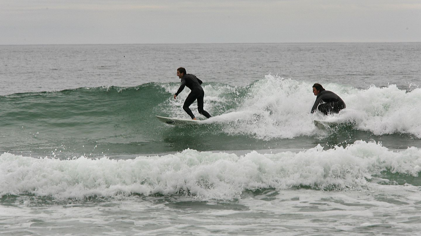 At Scarborough Beach State Park, surfers work the waves on a gray day.