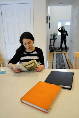 Carolyn Zhou reads from Mark Twain's Adventures of Huckleberry Finn at the kitchen table for English class homework while her sister Megan, 14, preps for a soccer team practice.