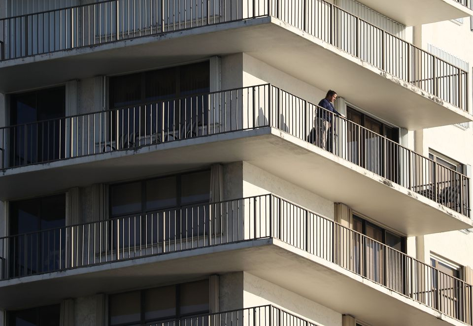 An FBI agent looked out from a balcony of a condominium in the building that has a possible connection to mail-bomb suspect Cesar Sayoc and his mother on Friday.
