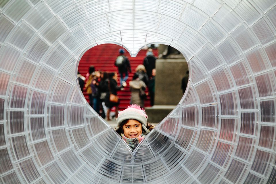 A little girl poses for photos in Aranda\Lasch + Marcelo Coelho's 'Window to the Heart' in Times Square in New York City.