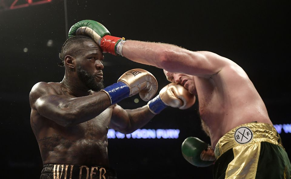 Deontay Wilder (left) and Tyson Fury trade punches during a WBC heavyweight championship boxing match.