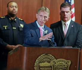 Boston Police Commissioner William Evans is pictured at the podium, with Boston Mayor Martin Walsh at right and Boston Police Superintendent-In-Chief William Gross at left.