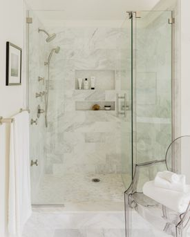 The honed pearl marble of the shower matches the main space floor.