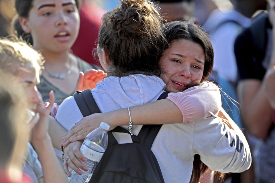Students released from a lockdown embraced following a shooting at Marjory Stoneman Douglas High School in Parkland, Fla.