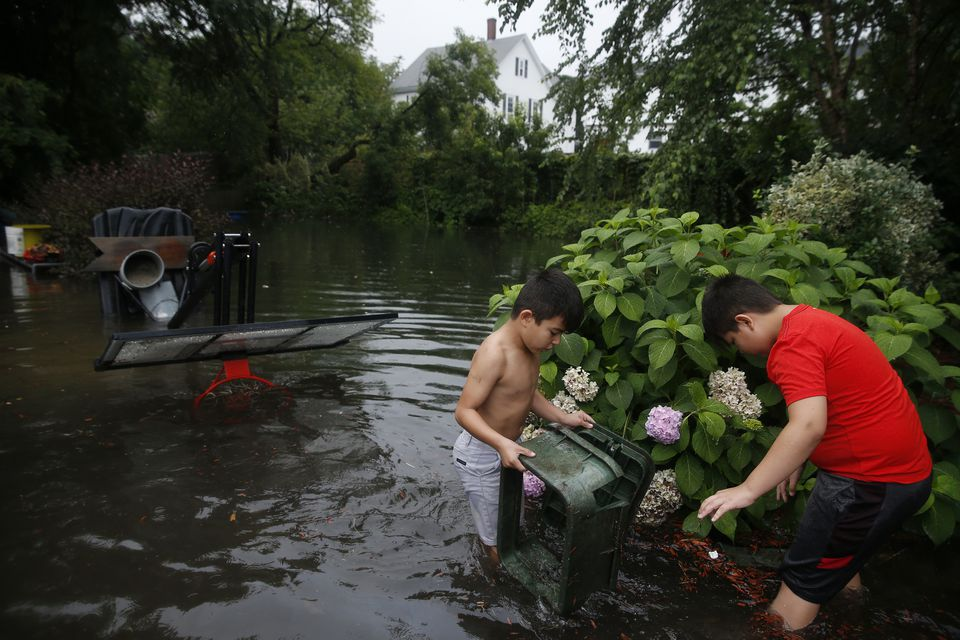 Angel Cardenas (left), 7, of Lynn, and his brother Chris, 10, picked up a chair that they found in the flood waters surrounding their home.