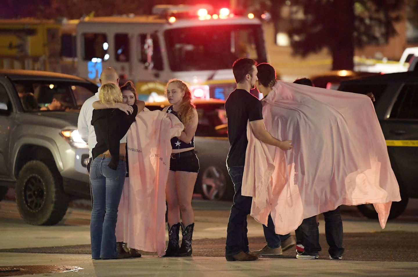 People comforted each other as they stand near the scene.