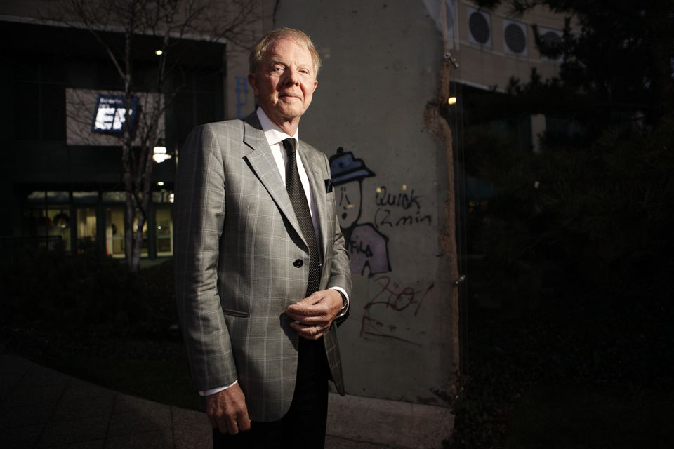 Bertil Hult, founder of EF Education First, in front of a piece of the Berlin Wall at the company's Cambridge office. EF is doubling the size of its Cambridge campus.