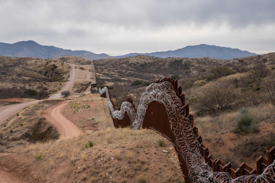 The US border fence, with concertina wire, outside Nogales, Arizona.