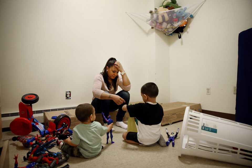 Lany Ruiz (center) sat with her children Joshua Ruiz, 18-months (left) and Alex, 5, while they played in the boys bedroom. Lany sat on the unassembled bunk beds she recently bought with her tax return.