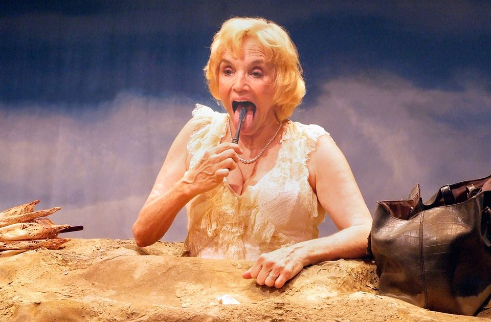"As Winnie, Brooke Adams brushes her teeth while buried in sand in ""Happy Days"" at Babson College."