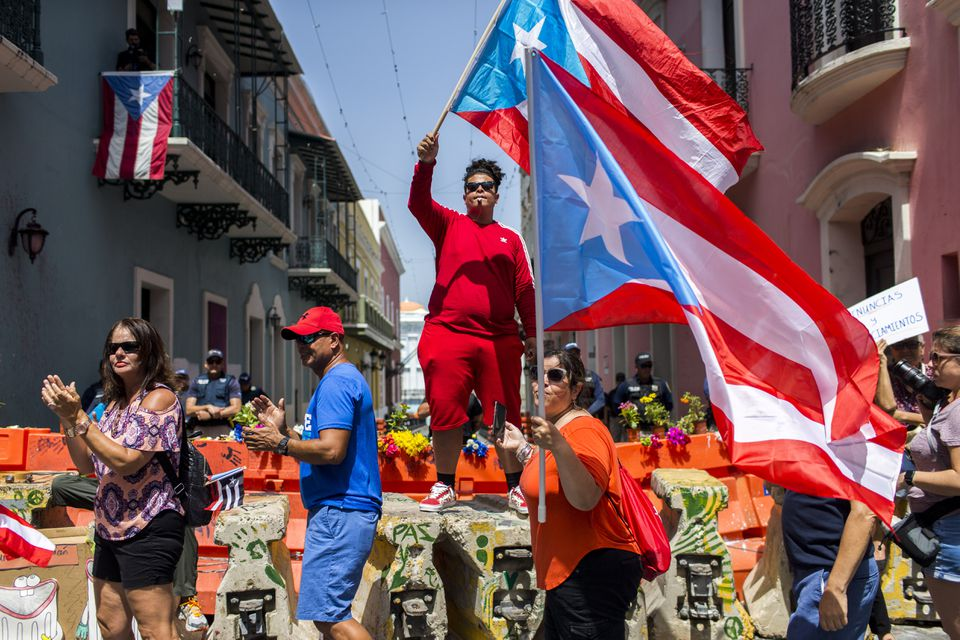 Demonstrators waved Puerto Rican national flags in front of the governor's mansion in San Juan on Wednesday as part of a protest calling for Governor Ricardo Rosselló to resign.