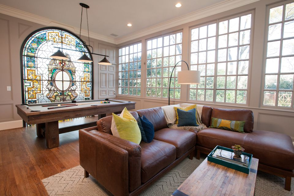 This living room in Atlanta has high ceilings. The Property Brothers gave it an entertaining feel with leather couches, a custom pool table, and new hardwood floors.
