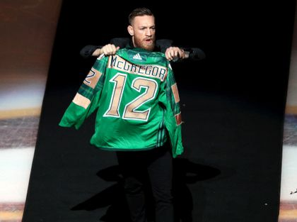 c452fc466a3 MMA fighter Connor McGregor waved a green Bruins sweater as he came out for  the ceremonial