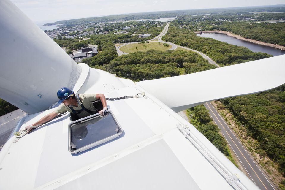 Sumul Shah, CEO of Solaya Energy, climbs on a wind turbine at Gloucester's Blackburn Industrial Park.