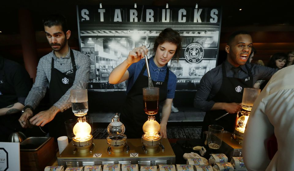 Starbucks workers prepared coffee using siphon vacuum coffee makers at a station in the lobby of the coffee company's annual shareholders meeting in Seattle.