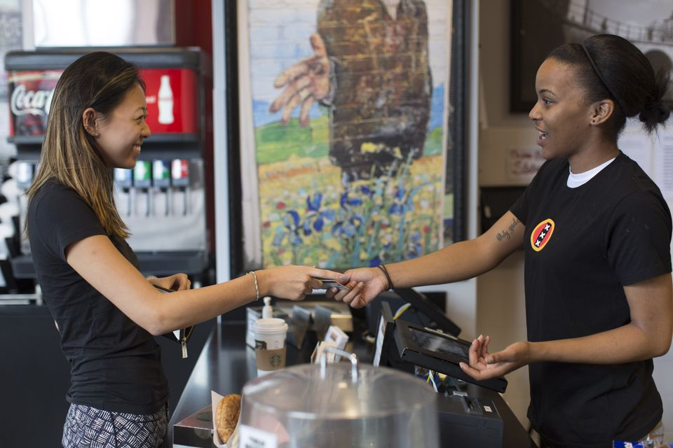 Sophia Ling, of Norfolk, pays Amsterdam Falafelshop employee Trecell Ellis using a credit card.