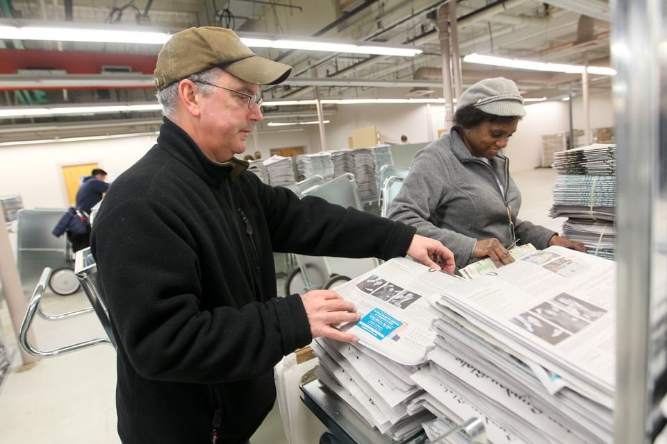 Globe employees Sean Murphy and Paula Bouknight worked to get newspapers ready for delivery.