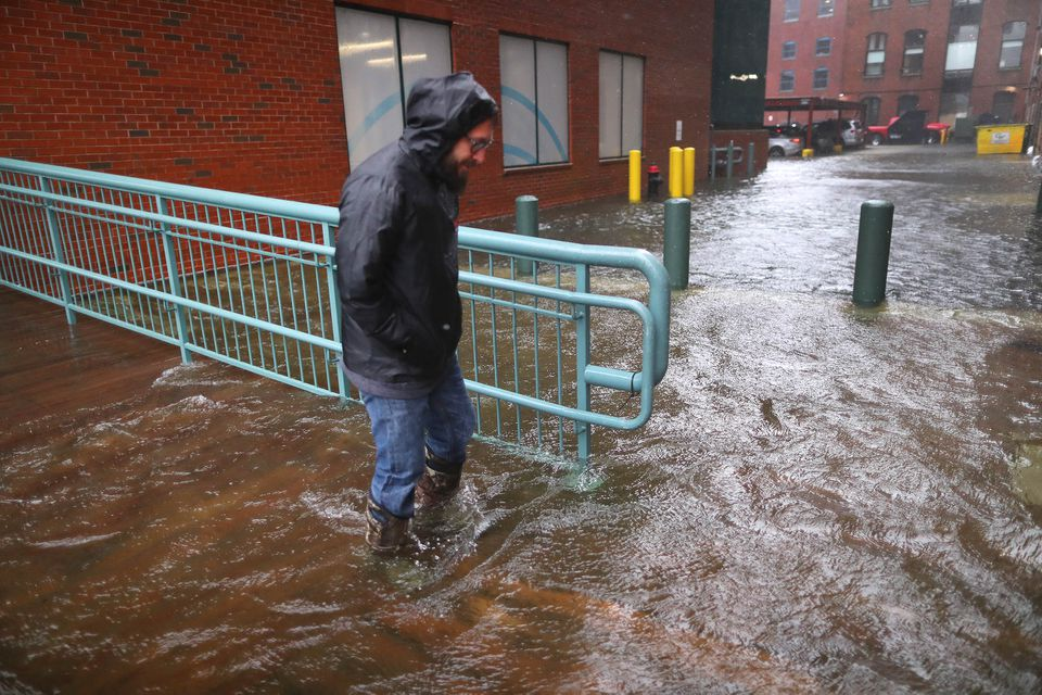A man walks slowly through a flooded back street off Congress Street, where water was flowing over from Fort Point Channel in the Seaport district.