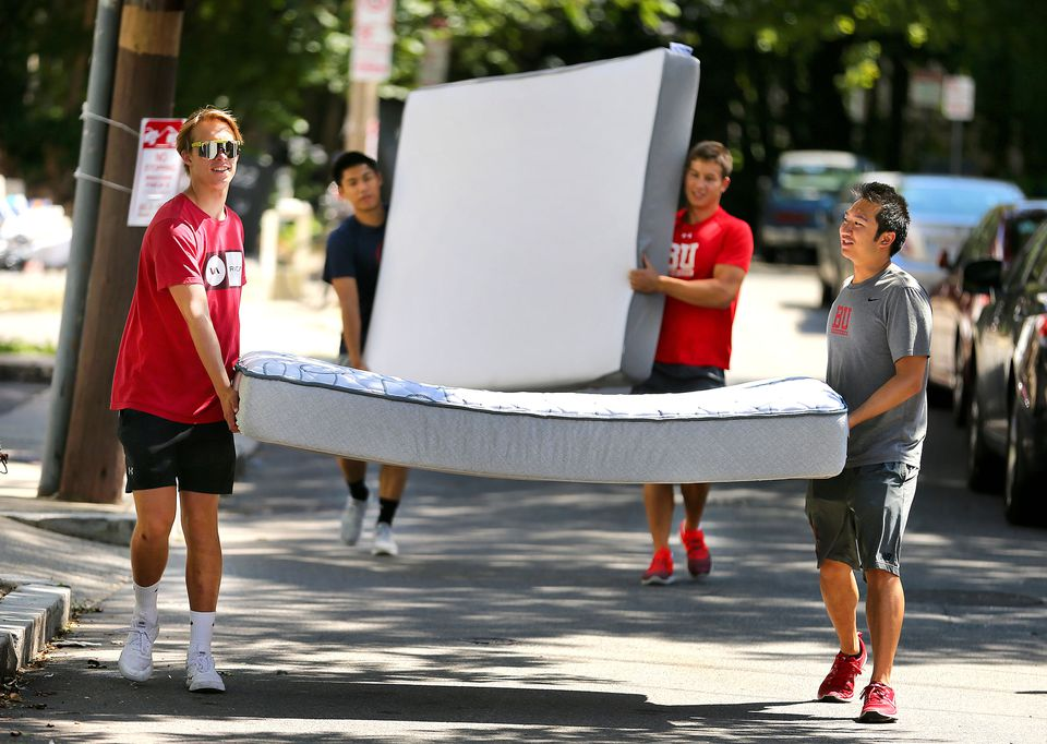 Boston University students carried a mattress and box spring down Wardsworth Street in Allston to a nearby apartment.
